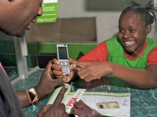 An M-PESA agent assists a customer, Kenya.