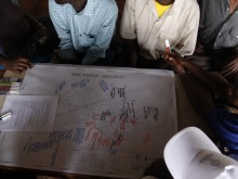 Kibera residents mark security problems on a map overlay before uploading to the online digital version.