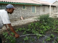 A Kaputiei New Town resident waters his garden.