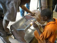 Local auto mechanic welding two oil drums together for a Digital Drum, Kampala.