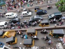 Motorbikes, motorized rickshaws, cars, bicycles, and pedestrians share congested traffic lanes in Chennai's T Nagar district.