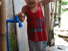 A boy showers with water from an individual house pipe, Baybay Sapa informal settlement, Antipolo City, Rizal province.